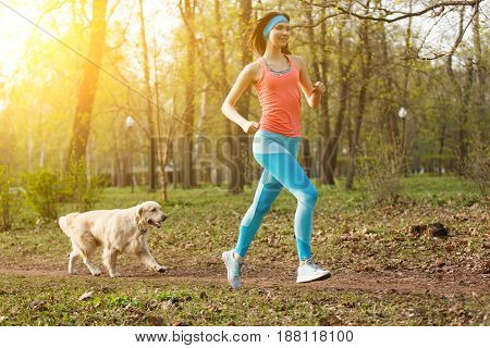 Girl with labrador for jog in park