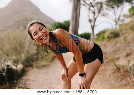 Healthy young woman standing on mountain trail with her hands on knees and laughing. Asian female runner in sportswear taking a break after running workout.