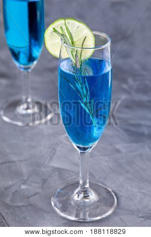 blue curacao cocktail with rosemary, lime and lemond on a concrete background. vertical