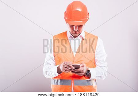 Foreman Wearing Reflective Vest Browsing Or Texting On Smartphone