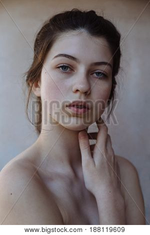 Beautiful Face of Young Girl with Clean Fresh Skin close up on grey background. Beauty Fine Art Portrait. Beautiful Spa Woman Smiling. Perfect Fresh Skin. Pure Beauty Model. Youth and Skin Care Concept