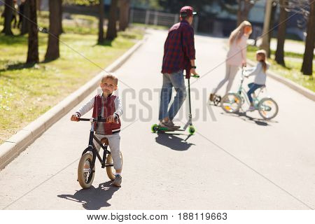 Couple with children in active walk on scooters at park
