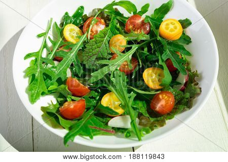 Fresh arugula salad with kumquat and tomato cherry on white wooden background. Top view. Healthy food. Diet