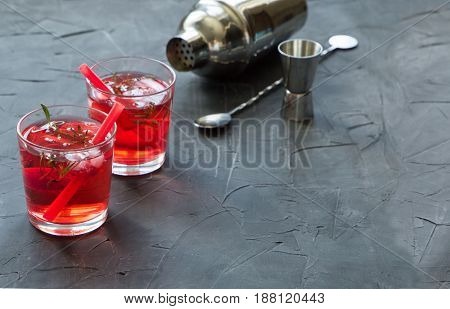 Red drink with ice. Cocktail making bar tools, strawberry and thyme leaves on a concrete background. space for text