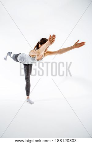 Woman balancing on one leg at isolated background