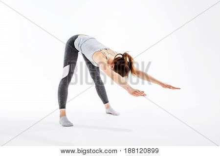 Young athlete practicing in yoga on isolated background