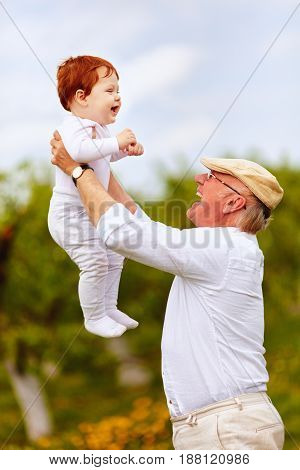 happy grandpa playing with infant grandson in spring garden