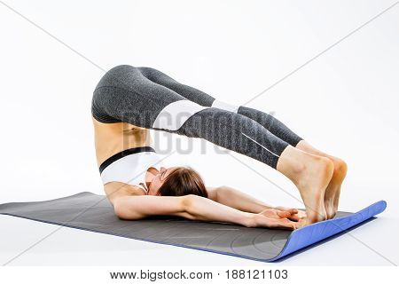 Woman doing stretching on rug at isolated background