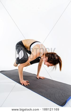 Sportswoman stands on hands at rug on empty background