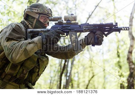 Military sniper on task in woods during day