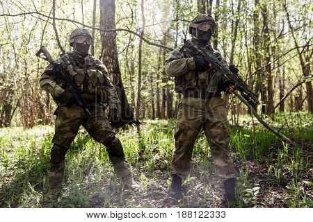 Two soldiers with machine guns in forest on reconnaissance