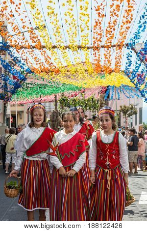 ESTREITO DE CAMARA DE LOBOS PORTUGAL - SEPTEMBER 10 2016: Girls wearing in traditional costumes at Madeira Wine Festival in Estreito de Camara de Lobos Madeira Portugal. The Madeira Wine Festival honors the grape harvest with a celebration of traditional