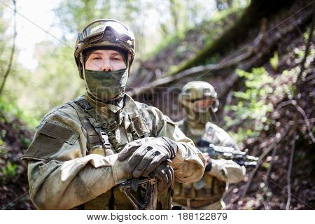 Military men in helmet and camouflage with gun on forest background