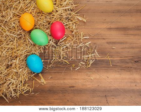 Rural eco background with colored chicken eggs and straw on the background of old wooden planks. The view from the top. Creative background for Easter cards, menu or advertising