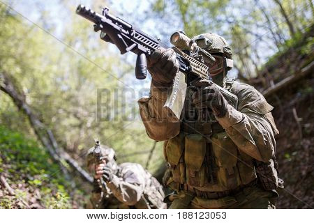 Group officers on military mission in woods during day