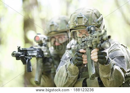 Photo of soldiers with submachine-gun in woods during day