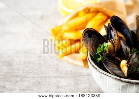 Mussels With Herbs In A Bowl With Lemon And French Fries On A Wh