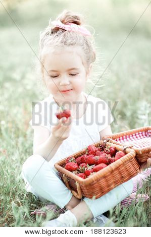 Cute kid girl 4-5 year old holding strawberry outdoors. Summer time.