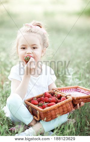 Cute baby girl 4-5 year old eating fresh strawberry sitting in park. Looking at camera. Childhood.