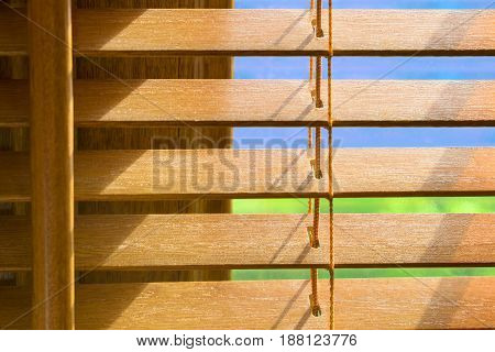 Brown wooden blinds that are slighlty open showing blue sky on a bright sunny day