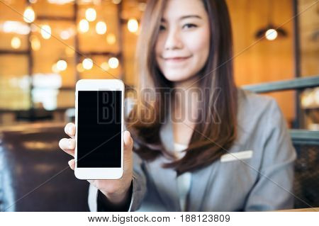 Mockup image of an Asian beautiful business woman holding and showing white mobile phone with blank black screen in cafe