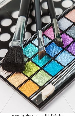 Brushes and makeup palette. Focus on pallets in the center of the frame