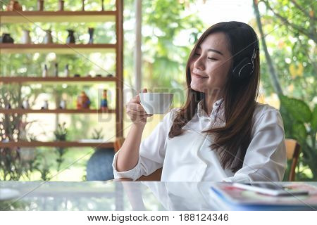 A beautiful Asian woman close her eyes and listening to music with headphone while drinking coffee with feeling happy and relax in cafe with green nature background