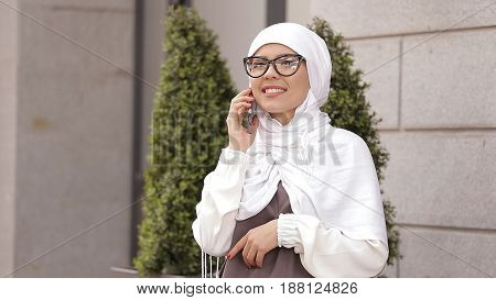 Young Muslim Girl Uses Smartphone and Laughing.