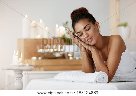 Young tender african girl smiling resting relaxing with closed eyes in spa salon.