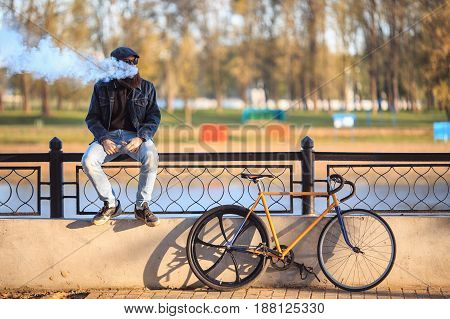 Vape In Real Life. Young Man With Gourgeous Large Beard And In Sunglasses And In The Cap Having A Re