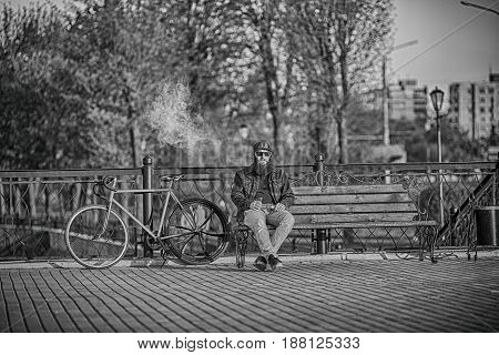 Vape In Life. Young Man With Large Beard In Sunglasses And In The Cap Having A Rest And Vaping An El