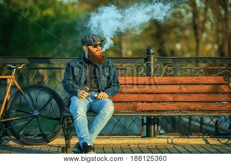 Vape In Life. Young Man With Gourgeous Large Beard In Sunglasses And In The Cap Having A Rest And Va