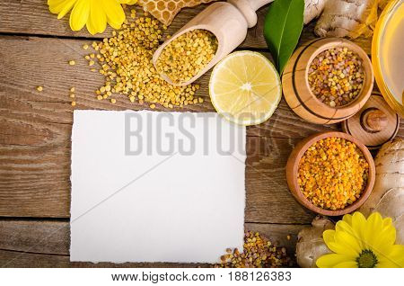 Honeycombs ,honey, Ginger, Pollen, Lemon On A Wooden Table And Empty Card For You Text . Top View