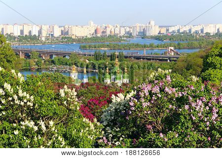 Spring view of Kyiv with Vydubychi monastery, Darnytsky bridge over Dnipro river and lilac blossom in botanical garden, Ukraine