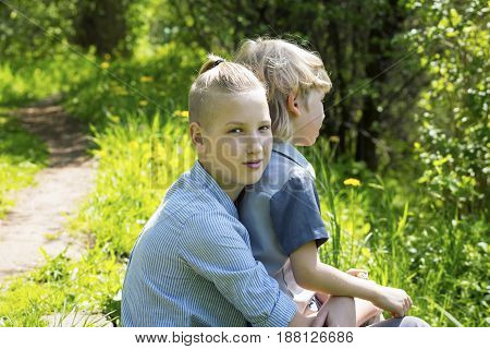 Brothers sitting on the grass in the park. Elder brother concept