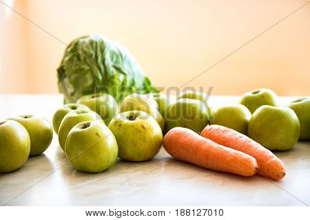 Two orange carrots green apples bunch of dill and head of cabbage on the table. Close-up view. Orange background