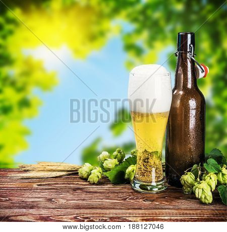 glass of beer and an empty bottle on the table on nature background