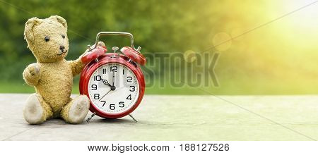 School vacation summer holiday time concept - web banner of a toy bear and alarm clock