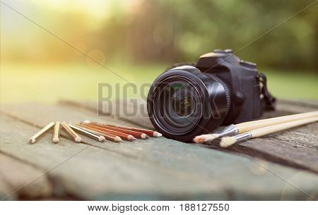 Graphic designer and photographer tools - camera with pencils and brushes