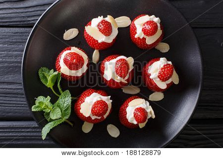 Fresh Strawberries With Almonds And Whipped Cream On A Plate Close-up. Horizontal Top View