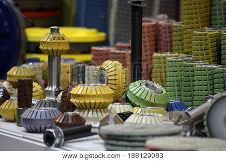 Grinding discs and milling tools in various shapes and colours, neatly arranged in line