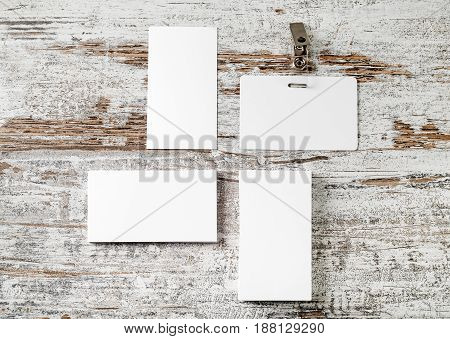 Bank business cards and badge on vintage wooden table background. Mock up for placing your design. Template for ID. Top view.