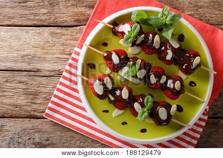 Skewers With Fresh Strawberries Are Decorated With Chocolate, Mint And Almonds. Horizontal Top View