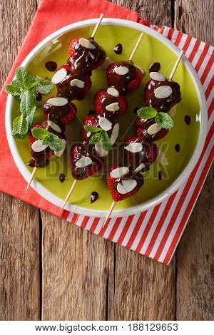 Skewers With Fresh Strawberries Are Decorated With Chocolate, Mint And Almonds. Vertical Top View