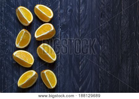 Pieces of oranges on dark table with empty space for text