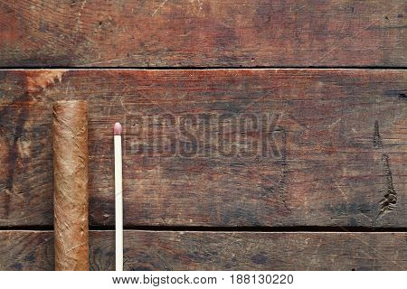 One Cuban cigar near matchstick on old wooden background