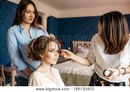 A hairdresser and make-up artist prepare the bride for the wedding day. Background is the interior of the room in blue colors