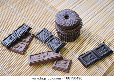 Round chocolate cookie ring and chocolate pieces lie on a bamboo background