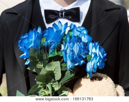 A man in a classic suit with a bouquet of blue roses
