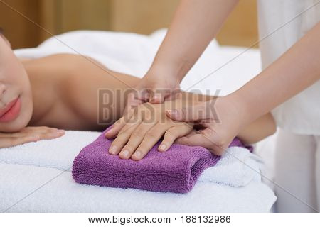 Close-up shot of female hand lying on terry towel and being massaged by therapist in beauty salon